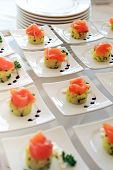 stock photo of buffet catering  - Display of gourmet individual plates of smoked salmon appetizers on display on a buffet table or banquet at a catered event - JPG