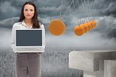 pic of newton  - Brunette woman standing while showing a laptop screen against newtons cradle above city - JPG