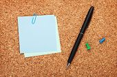 Blank postit notes on cork notice board with pen