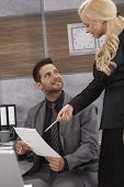 Young businessman listening to attractive female boss with adoration.