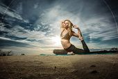 Woman practicing yoga outdoors over sunset sky background.