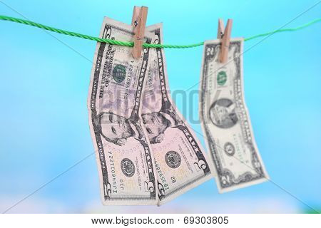 Dollar bills hanging on rope attached with clothes pins. Money-laundering concept. On bright background.