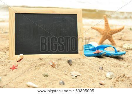 Blank chalkboard on beach background
