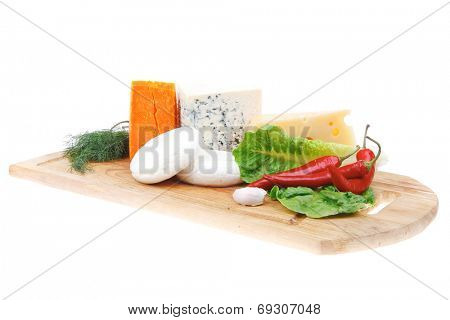 several  delicatessen types of cheese on wooden board with hot peppers and dill isolated on white background
