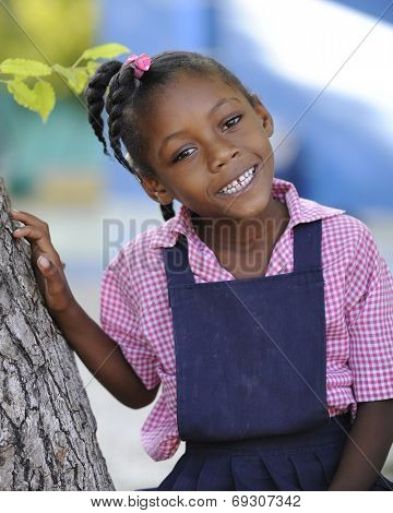 A happy Haitian elementary girl sitting in a tree in her school uniform.