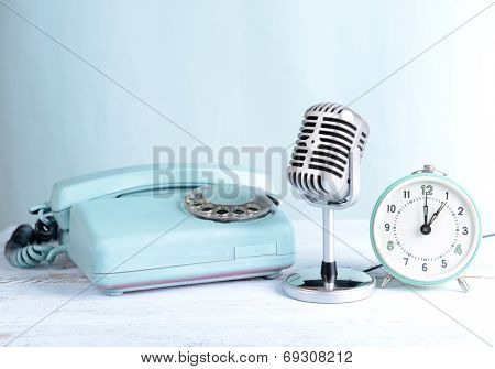 Vintage microphone,phone and alarm clock on table on light blue background