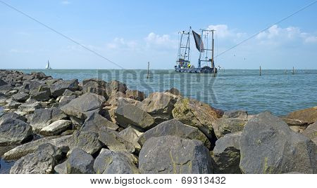 Trawler fishing on a lake along a dike