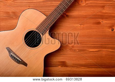 Close-up western guitar on brown wooden background