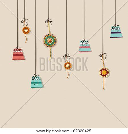 Beautiful greeting card design with hanging colorful gift boxes and rakhi on grey background for Hindu community festival Raksha Bandhan celebrations.