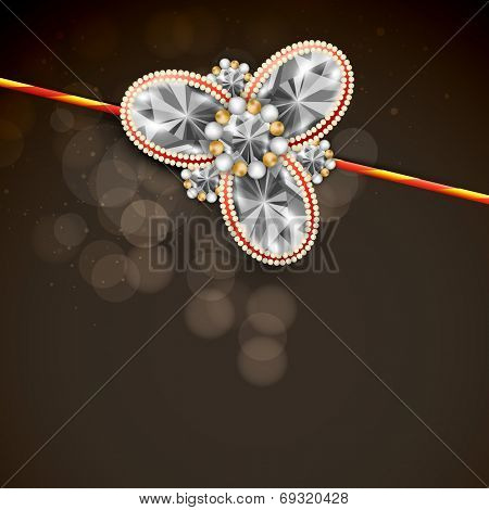 Shiny diamonds decorated rakhi on brown background for Hindu community festival Raksha Bandhan celebrations.