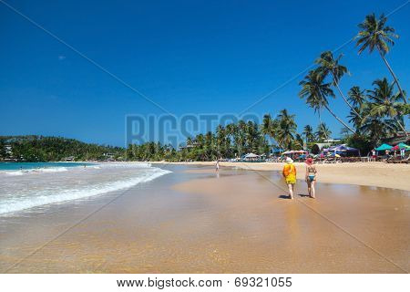 WELIGAMA, SRI LANKA - MARCH 5, 2014: Tourists walking on beautiful sandy beach. Tourism and fishing are two main businesses in this village.