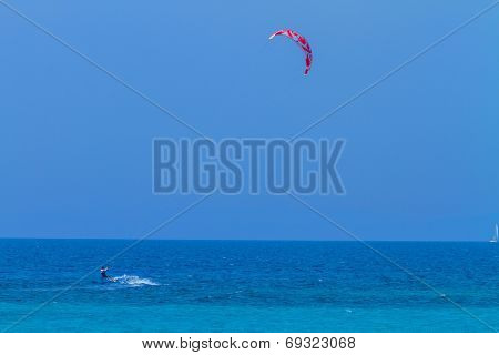 young kiter in the surrounding of turquoise sea kiting in Lefkas Greece