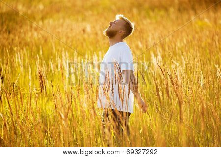 Happy Man Stands Among The Meadow Grass