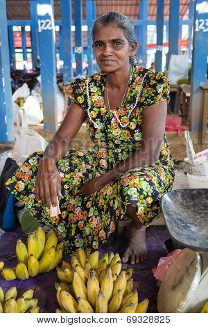 HIKKADUWA, SRI LANKA - MARCH 9, 2014: Local female vendor selling bananas. The Sunday market is a fantastic way to see Hikkaduwa's local life come alive along with fresh produce and local delicacy