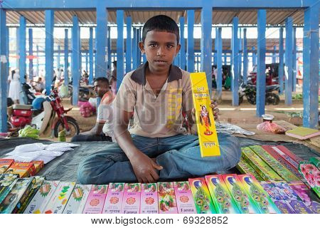 HIKKADUWA, SRI LANKA - MARCH 9, 2014: Young local vendor selling scent sticks. The Sunday market is great way to see local life come alive along with fresh produce and local delicacy