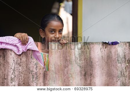 WELIGAMA, SRI LANKA - MARCH 8, 2014: Local girl behind wooden fence. Local people in Sri Lanka are very friendly to tourists.