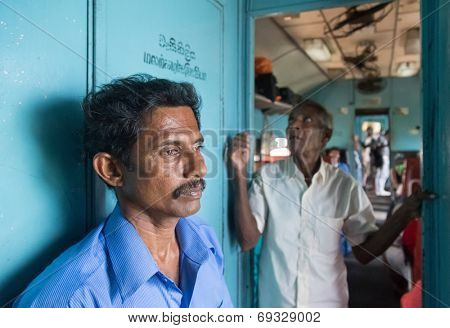 HIKKADUWA, SRI LANKA - MARCH 12, 2014: Two local men standing in train. Trains are very cheap and poorly maintained but it's the best option to witness a bit of everyday local life.