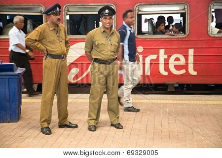 COLOMBO, SRI LANKA - MARCH 12, 2014: Two policemen standing at the train station. The police force has a manpower of approximately 85,000.