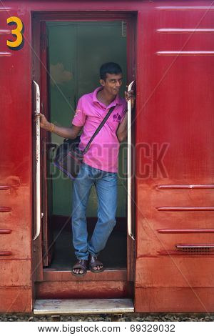 HIKKADUWA, SRI LANKA - MARCH 12, 2014: Local man standing at wagon entrance. Trains are very cheap and poorly maintained but it's the best option to witness a bit of everyday local life.