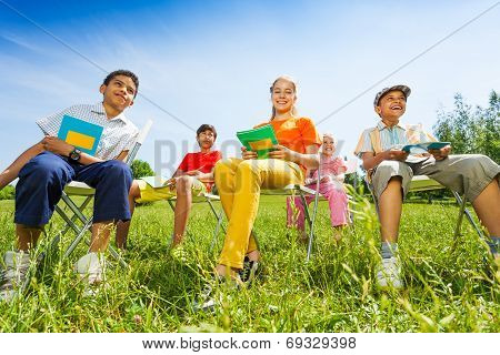 Happy children hold exercise books and sit
