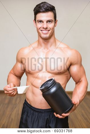Portrait of a shirtless body builder holding a scoop of protein mix in gym