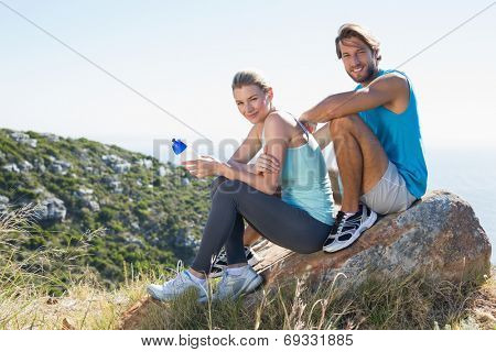 Fit couple taking a break at summit smiling at camera on a sunny day