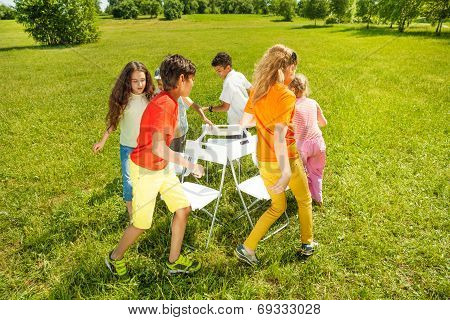 Kids run around playing musical chairs game