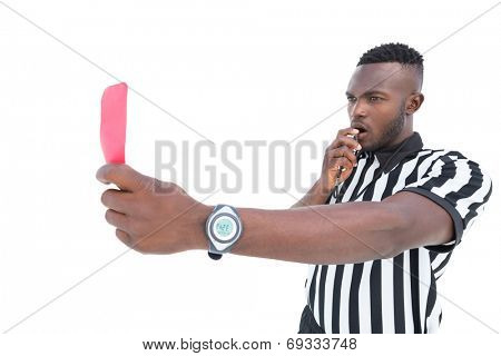 Serious referee showing red card blowing whistle on white background