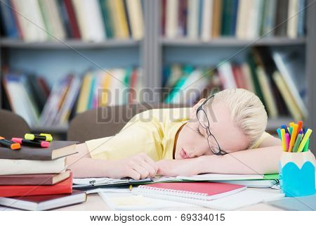 Tired student with glasses sleeping in library