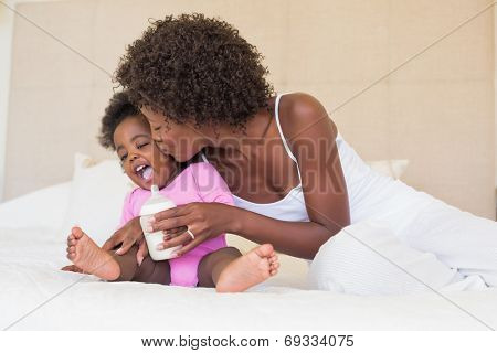 Happy parents with baby girl on their bed at home in the bedroom