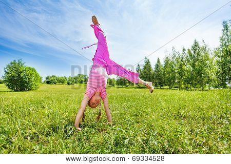 Girl making flip on grass standing upside down
