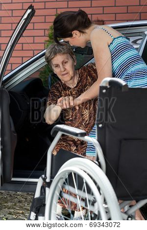 Woman Helping Her Grandmother Get Into The Car