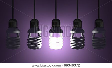 Glowing Spiral Light Bulb Hanging Among Dead Ones