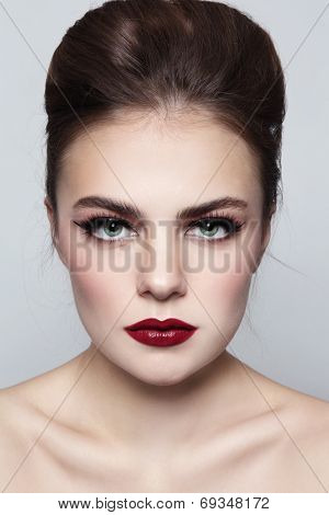 Portrait of young beautiful woman with hair bun and red lipstick
