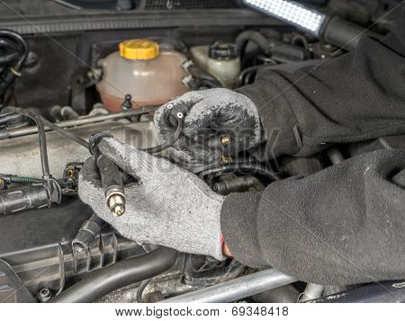 Auto mechanic replacing broken Diesel glow plug wire in car diesel engine compartment