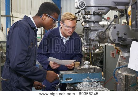 Engineer Showing Apprentice How To Use Drill In Factory