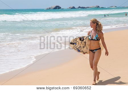 HIKKADUWA, SRI LANKA - FEBRUARY 24, 2014: Young woman walking the beach carrying surf board. Hikkaduwa is well known tourist international destination for board surfing.