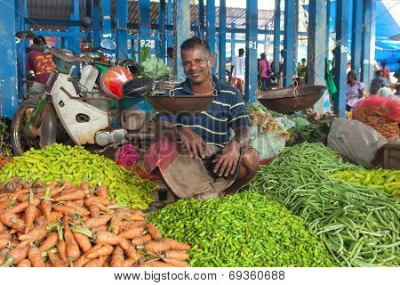 HIKKADUWA, SRI LANKA - FEBRUARY 23, 2014: Portrait of vendor selling his produce. The Sunday market is great way to see Hikkaduwa's local life come alive along with fresh produce and local delicacy