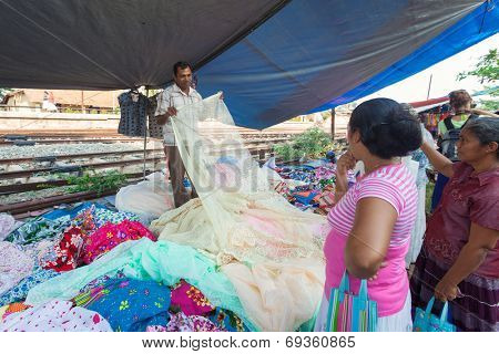 HIKKADUWA, SRI LANKA - FEBRUARY 23, 2014: Local women buying textile from street vendor. The Sunday market is a fantastic way to see local life come alive along with fresh produce and local delicacy.