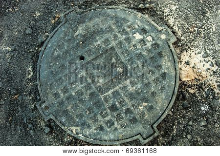 Manhole With Metal Cover In Asphalt Surface