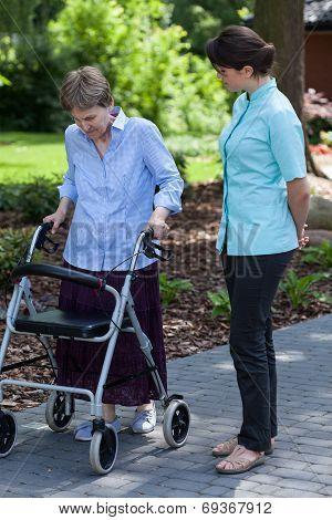 Nurse Watches As An Elderly Woman Walks