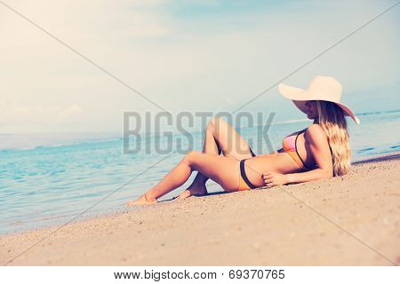 Young fashion woman relaxing on warm tropical beach, retro style color tone