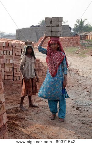 SARBERIA,INDIA, JANUARY 16: Brick field workers carrying complete finish brick from the kiln. Tools and machines for making bricks are very rudimentary, Jan 14, 2009 in Sarberia, West Bengal, India.