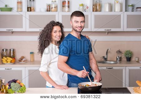 Beautiful couple preparing supper together in kitchen