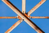 picture of girder  - Worn metal girders crossing held together with plates and screws - JPG