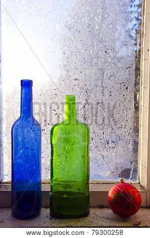 New Year Christmas Toy And Two Old Bottle On Winter Window With Frost