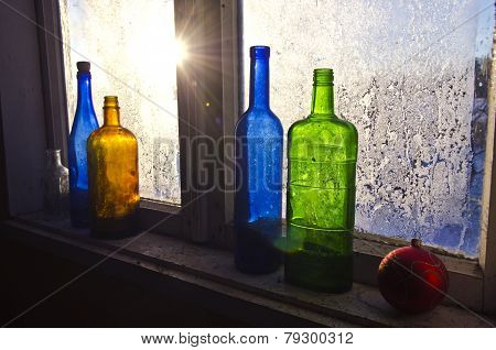 Colorful Glass Bottles On Winter Old Farm Window With Hoarfrost Ice