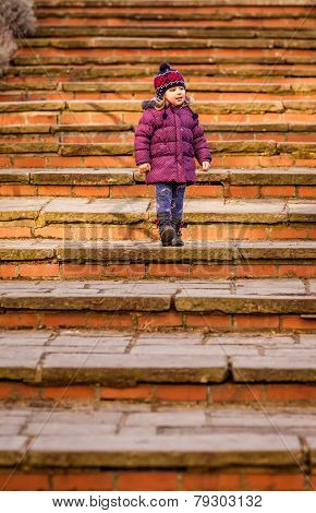 Baby girl walking down old stairs