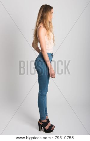 Blonde Girl Wearing Blue Jeans And T-shirt. Studio Shot