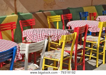 colorful chairs and tables with red checked tablecloth in a street of Novi Sad, Serbia